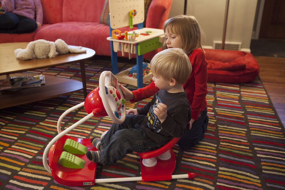Mazie showing Tyler how to use his new car toy.